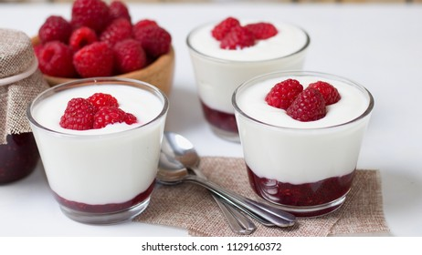 White yogurt with whole ripe raspberries and wooden bowl full of juicy fruit. Wide screen