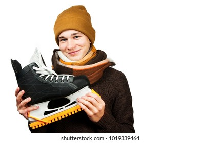 White young guy in a hat and sweater and scarf, holds skates in his hands, isolated on a white background.