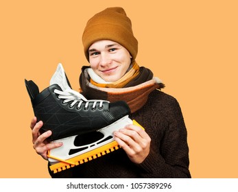White young guy in a hat and sweater and scarf, holds skates in his hands. Isolated on a orange background.