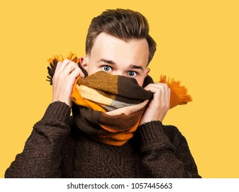 White young guy in sweaer hiding his face in scarf. Isolated on yellow background.