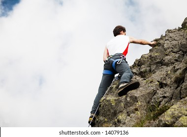 White young male rock-climber, summer season, upward view, horizontal frame, vibrant colours, copy-space on the left