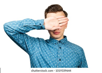 White young man dressed in blue shirt closes eyes with her hands, isolated on white background