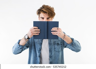 White young man reads and hides his face behind a book. Studio portrait of guy with fashion hair wearing a jeans shirt.