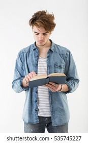 White young man standing up on white background while reads a book. Studio portrait of guy with fashion hair wearing a jeans shirt.