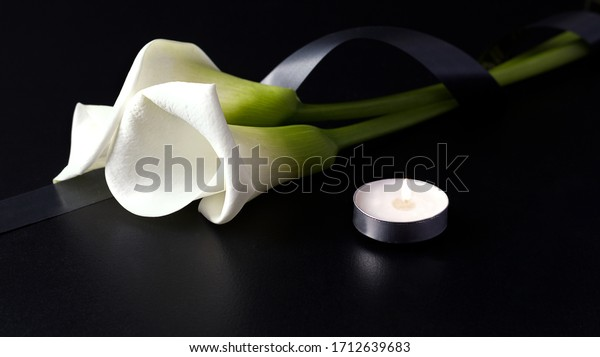 White Zantedesia with mourning ribbon and burning candles on a black background. Concept of sorrow and death