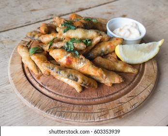 Whitebait, small fried fish served on a wooden rustic platter and wooden table with a dip and lemon.