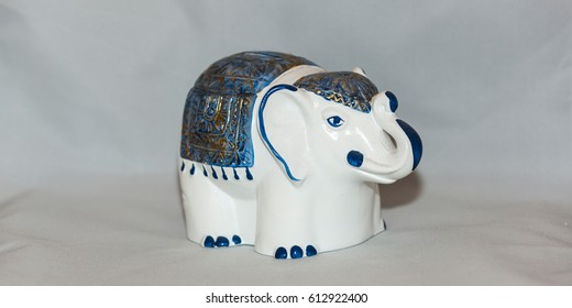 White-blue clay coin box for money in the form of an elephant