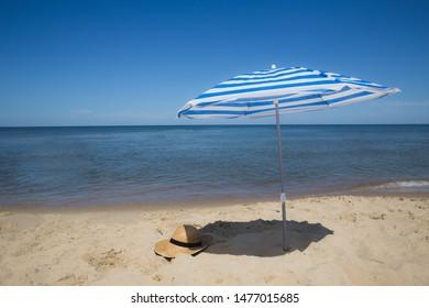 White-blue umbrella stuck in the sand on the seashore. Seashore umbrella.
