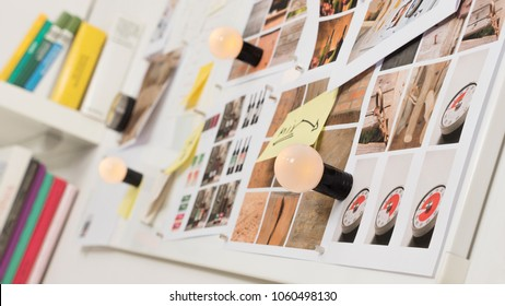 Whiteboard with photographs, burning light bulbs and memos on sticky notes on a magnetic wall next to a blurred book rack in a design studio, nobody