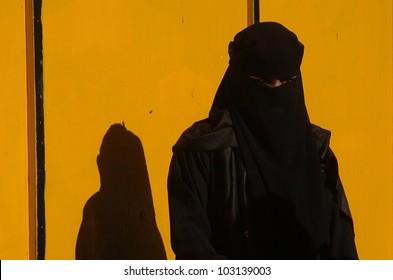 Whitechapel - East London - England - 2004. A Muslim woman stands by a yellow wall in Whitechapel, east London, England. UK, 2004.