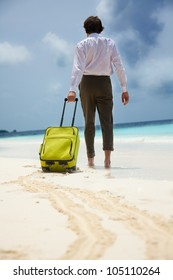 White-collar worker on the beach vacation - walking with green suitcase