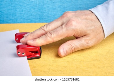 White-collar worker punching holes in sheet of paper, using red steel hole puncher, close-up of hand with white sleeve.