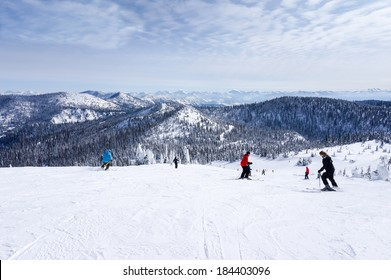 WHITEFISH, MONTANA-MARCH 24: Skiers descend from the summit at Whitefish Mountain Resort March 24, 2014. At a summit elevation of 6,817ft, Glacier National Park is visible at a distance on this day.
