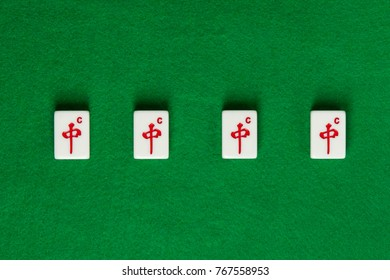 White-green tiles for mahjong on green cloth. 4 dragons