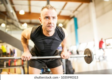 white-haired man in black lifting bar with weight in gym