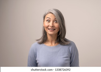 White-Haired Mongolian Woman on a White Bckground. On Her Face There is a Surprised Look. Her Eyes are Wide Open. Close Up Shoot.