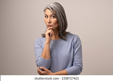 A White-Haired Mongolian Woman with a Thoughtful Look. Her Hand is Raised to Her Chin. On the Background of Women Gray. Mongolian Beauty Concept. Close Up Shoot.
