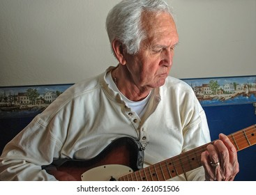 White-haired older caucasian male playing guitar for his own pleasure in casual surrounding of his own home.