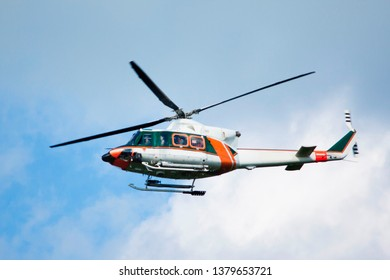 White-orange helicopter is flying in blue sky