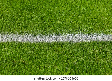 A white-painted line on a green football field in the afternoon