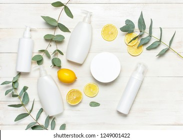 Whites Cosmetic bottle containers, fresh lemon eucalyptus on white wooden background top view flat lay copy space. Blank label for branding mock-up Natural beauty product concept Shower Gel Soap Cream