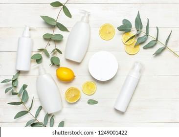 Weiße Kosmetische Flaschenbehältnisse, frischer Zitroneneukalyptus auf weißem Holzhintergrund, Draufsicht flach, Kopienraum. Leere Kennzeichnung für Branding-Modell Naturschönheitsprodukt-Konzept Dusche Gel-Seife Creme