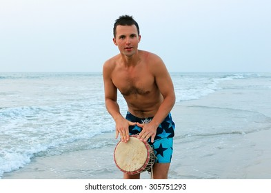 white-skin man playing the African drum on sea background like a mantra