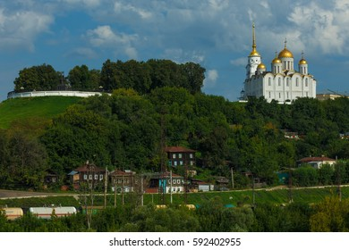 The white-stone Assumption Cathedral and the old city buildings at the bottom of the hill. Vladimir city, Russia.