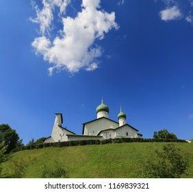 White-stone church against the blue sky, white clouds and green grass