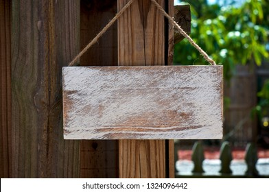 A whitewashed blank sign board hanging from jute rope outdoors on old wooden fence.
