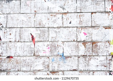 whitewashed brick wall with old faded white paint and old street posters bits