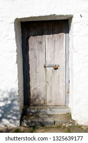 Whitewashed old cottage door locked with a padlocked bolt