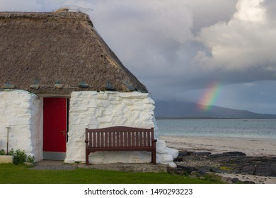 Whitewashed stone house with a thatched roof on a beach as a rainbow breaks over a cloudy sky