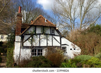 Whitewashed timbered cottage in a woodland setting somewhat reminiscent of an enchanted fairytale scene from childhood