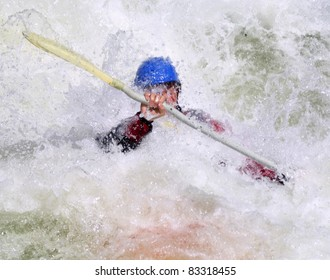 Whitewater kayaker in Fishermans Nightmare of Gore Canyon.  Crisp focus on his fist coming out of the water.
