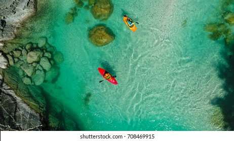 Whitewater Kayaker on the Emerald waters of Soca river, Slovenia, are the rafting paradise for adrenaline seekers and also nature lovers, aerial view.