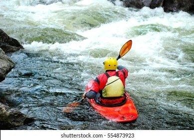A whitewater kayaker waiting to surf a wave in fast moving water on the river