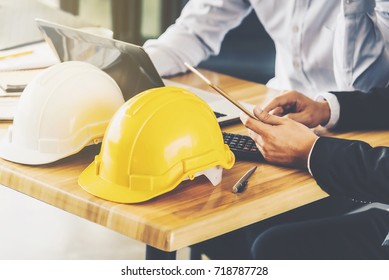 White,Yellow hard safety helmet hat for safety project of workmen On a wooden desk.Architect is the background blurred.