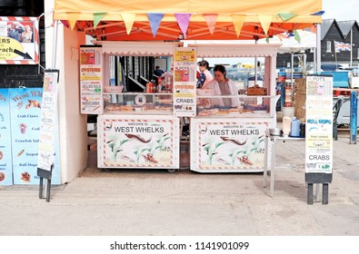 WHITSTABLE, ENGLAND - JUNE 17, 2018: A vendor at her seafood stall in Whitstable harbor pier, Whitstable, UK. Whitstable is famous for its Native Oysters which are collected since Roman times.