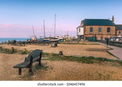 Whitstable, Kent, UK beach with wooden benches and old wooden boats moored on the beach. There is a red brick building and a pedestrian pathway. There equipment machinery of the oyster industry.
