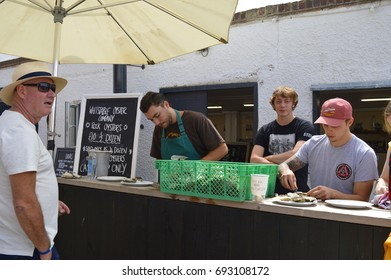 WHITSTABLE, UK-JULY 22: Fishmongers prepare and shuck oysters for the thousands of visitors that flock to the annual Oyster festival.July 22, 2017 in Whitstable, kent UK.