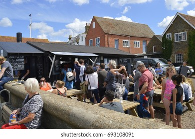 WHITSTABLE, UK-JULY 22: Visitors queue up at one of the many outlets selling oysters, during the world famous Oyster festival. July 22, 2017 in Whitstable, Kent, UK.