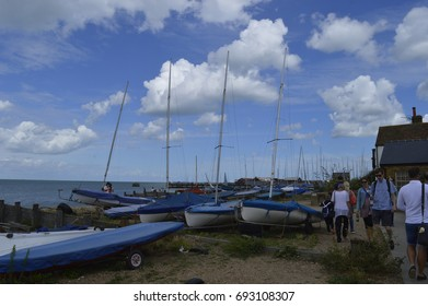 WHITSTABLE, UK-JULY 22: Visitors walk past the rows of docked boats in Whitstable during the world famous Oyster Festival. July 22, 2017 in Whitstable, Kent UK.
