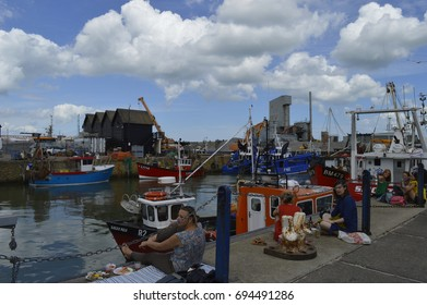 WHITSTABLE, UK-JULY 22:Visitors sitting by the harbour enjoying the oysters in the annual Whitstable Oyster Festival. July 22, 2017 in Whitstable kent UK.