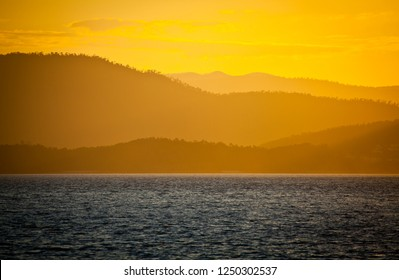 Whitsunday island sunset, Golden light illuminates forest covered islands in many shades of warm orange light in front of the ocean.