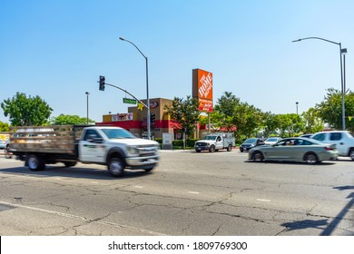 Whittier, CA / USA – September 3, 2020: View of passing traffic on Washington Blvd. in the City of Whittier, California, in front of a Carl's Jr restaurant and a Home Depot sign.