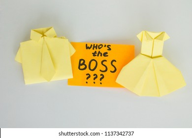 Who is the boss, inscription on note, an question mark. Management in business. The rights of men and women in the company. Shirt and a dress made of paper, origami. Sticker with an inscription.