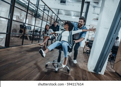 Who is the winner?  Four young cheerful business people in smart casual wear having fun while racing on office chairs and smiling