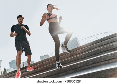 Who is going to come first? Full length low angle view of young couple in sport clothing running down the stairs together