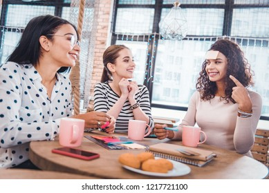 Who am I. Positive cheerful woman pointing at her note while sitting together with her friends